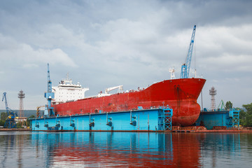 Big red tanker under repairing in blue floating dock