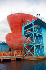 Bow of big red tanker under repairing in blue floating dock