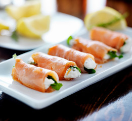 smoked salmon and arugul warp with cream cheese on platter