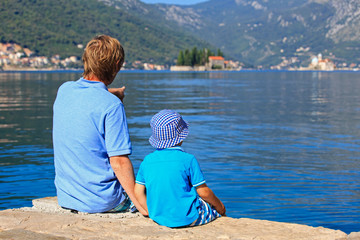 father and son looking at scenic view on sea vacation