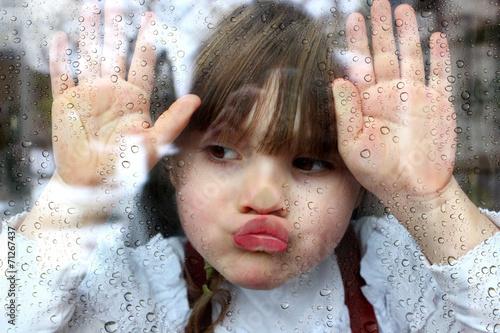 Novembertag: Portrait Mädchen klebt mit Gesicht und Händen an Fensterscheibe mit Regentropfen - 71267437