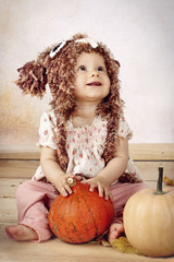Beautiful baby girl sitting with pumpkins wearing knitted hat