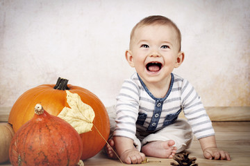 Laughing little baby sitting on the floor with pumpkins