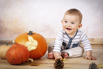 Smiling little baby sitting with pumpkins
