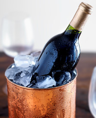 wine bottle in ice bucket with glasses