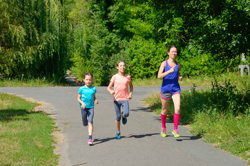 Family sport, mother and kids jogging outdoors, running in park