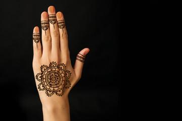 hand with mehendi on black background