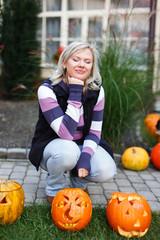 Woman squat at halloween pumpkins