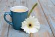 Постер, плакат: blauwe koffiekop met witte gerbera op oud hout
