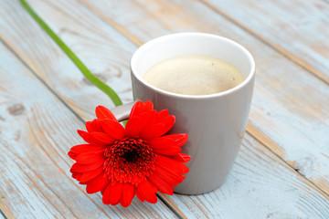 Koffiekop met rode gerbera op oud hout
