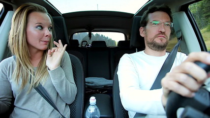 Unhappy couple fighting in car