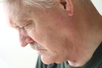 Depressed older man looking down