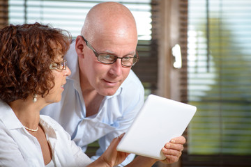a senior couple watching a digital tablet