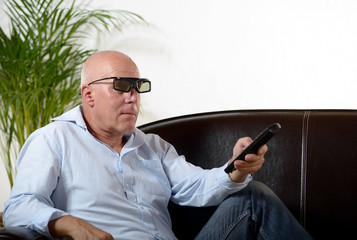 a man of mature age  watch TV with  3D glasses