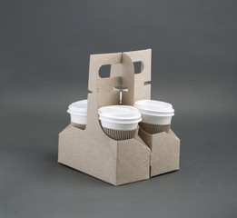 take-out coffee in holder on gray background.