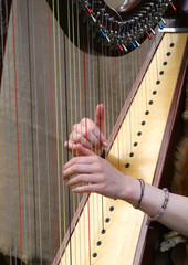 hands of woman strumming the strings of an ancient harp