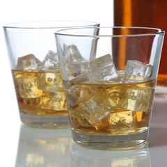 Whisky oder Whiskey im Glas und Flasche mit Eiswürfel