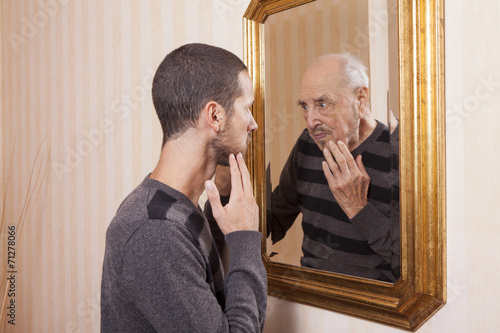 young man looking at an older himself in the mirror Poster