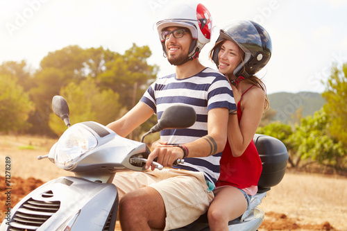 Young Couple Riding Motor Scooter Along Country Road - 71278289