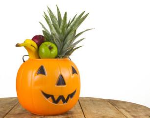 Halloween plastic pumpkin full of fruits
