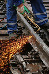 Welder using cutting torch to cut a rail