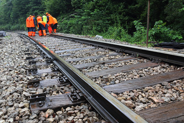 Workers in orange  raincoats repair railroad on rainy day
