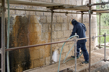 Worker cleans ancient stone wall with high pressure washer from