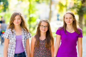 Teen schoolgirls walking in the park