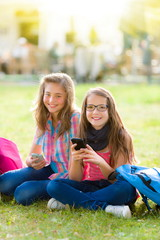 Teen schoolgirls having fun with mobile phone