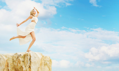 Blond woman trying to jump off the rock