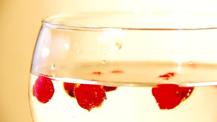 red berries floating in a glass of water