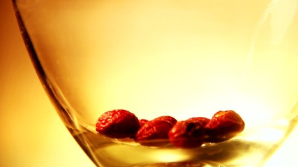 water being poured into a glass with red berries