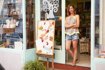 Female Owner Of Delicatessen Standing Outside Shop