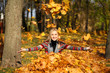 Happy woman drop up leaves in autumn park