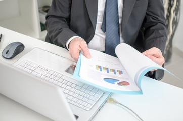 Businessman checking financial graphs