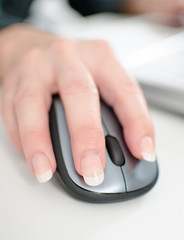 Businesswoman's hand holding a computer mouse
