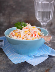 a salad of cabbage with grains of corn and crab sticks