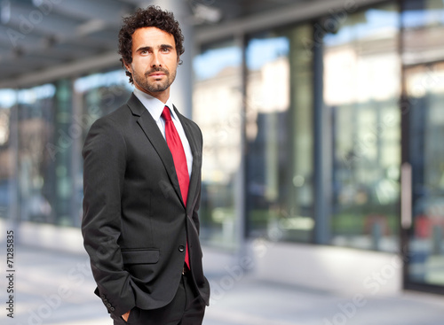 canvas print picture Handsome businessman against blurry background