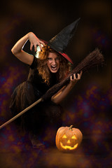 Young woman dressed like a witch. She is with broom and pumpkin.