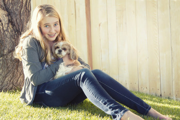 Teenage girl holding a small dog