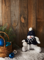Happy snowman and Christmas decoration on wooden plank.