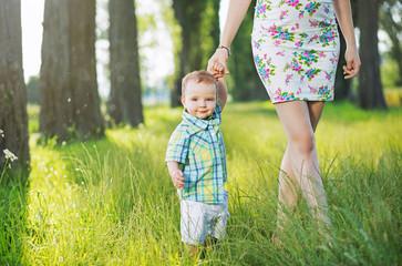 Cheerful kid holding mom's hand
