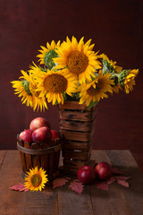 Still life with Sunflowers and apples on old wooden table