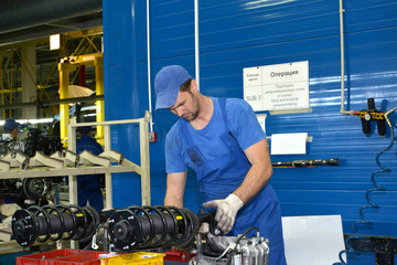 The worker selects depreciation racks for cars. Assembly shop of