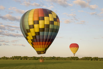 Two hot-air balloons in a field