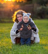 Happy young mother and her little son on the grass