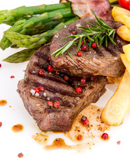 Tasty beef steaks on white background