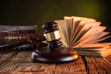 Photo: Wooden gavel and books on wooden table, law concept