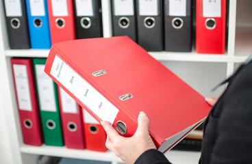 Businesswoman holding a red folder