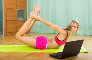 Female doing yoga with laptop
